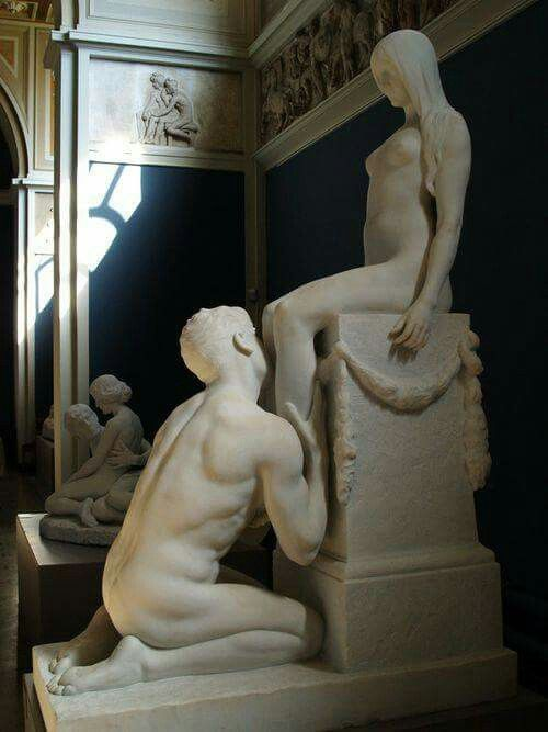 Sculpture of two lovers: man kneeling and touching feet of woman on pedestal. Both nude