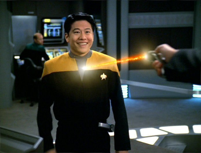 Image is a frame from Star Trek. The action is on board some Federation ship or other. A hand is seen firing a phaser weapon at a smiling Federation shipmate, whose uniform seems to be invincible against the weapon.