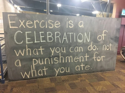 A chalkboard at a gym reads: Exercise is a celebration of what you can do, not a punishment for what you ate.