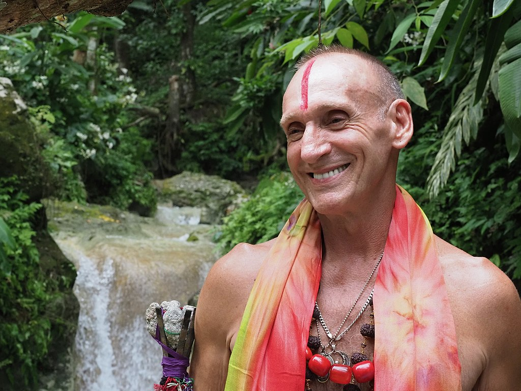 Shantaram's author standing in front of a waterfall with a jewelry necklace, a vertical line of red paint on his bald forehead, and a giant grin.