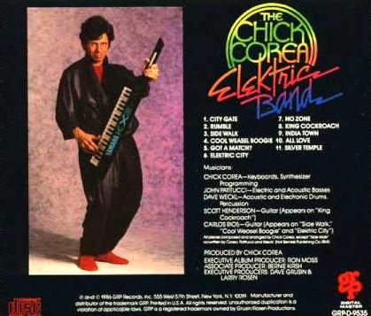 A page from a Chick Corea album booklet. It shows a standing Corea holding a small electronic keboard as if ready to play it, dressing in something that resembles a bath robe, along with red slippers. The rest of the image consists of a track listing, personnel information, and other data for the album.
