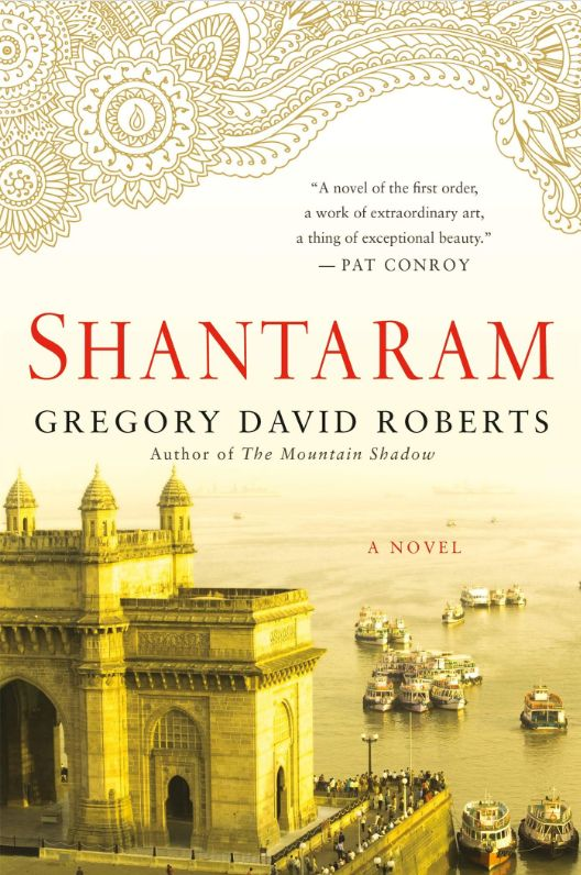 The cover of a paperback edition of Shantaram. It shows the book's title and authorship, plus a blurb, a building, and the sea.