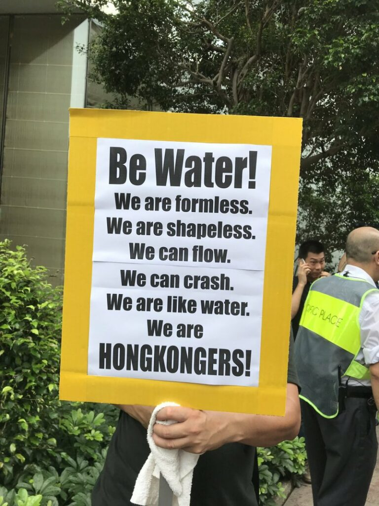 "A Hong Konger holds up a sign that reads: ""Be Water! We are formless. We are shapeless. We can flow. We can crash. We are like water. We are Hong Kongers!"""