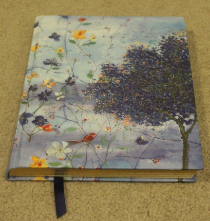 The image shows a blue hardback journal. The cover has impressionist-style art flowers, a tree, and a bay of sea.