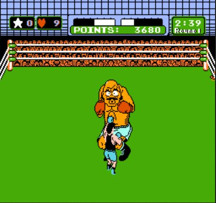 A screenshot of the video game Mike Tyson's Punch-Out!! from the 8-bit Nintendo Entertainment System. It shows a boxing ring, wherein the player, Little Mac, is jabbing an opponent, Bald Bull, with his left fist. Bald Bull is making a pained expression.