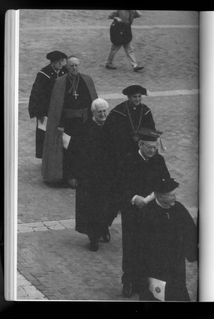 The image shows a black-and-white page from an academic catalog. It's a full page photo of six old white men in garb that is religious or academic or both: black robes, large crosses on necklaces, and so on. They are walking in a line, most of them smiling.