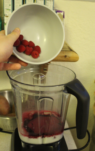 The photo shows the smoothie in progress. The photo shows my hand dumping a bowl of eight raspberries into the blender container.