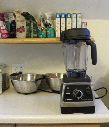 The photo shows a Vitamix blender atop my kitchen counter. In the background are various kitchen items, such as colanders and bags of quinoa.