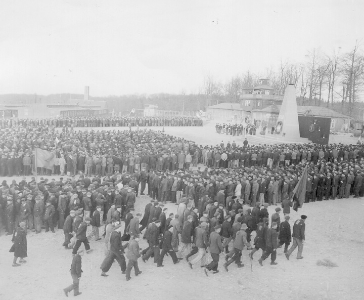 The black-and-white photograph shows the Buchenwald concentration camp in the bakground, with a rally in the foreground.