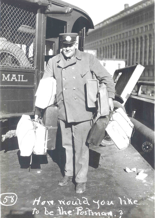 """The black-and-white image shows a frontal view of a mailman. Both his hands are full carrying suitcases, and he has suitcases under his arms as well. He's smiling and he has a uniform hat on. In the background is his mail vehicle. Words at the bottom say in white, """"How would you like to be the Postman?"""""""