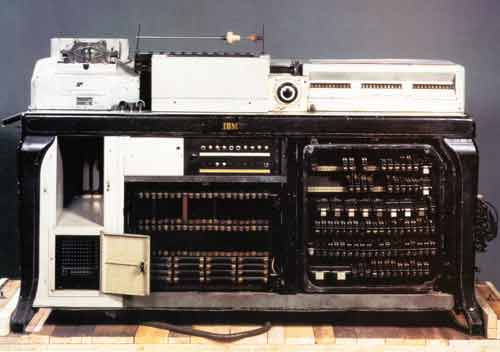 The color photo shows, sitting atop a wood board or table, an IBM Hollerith tabulator, which looks like a strange combination of a telephone, computer, sewing machine, and typewriter.
