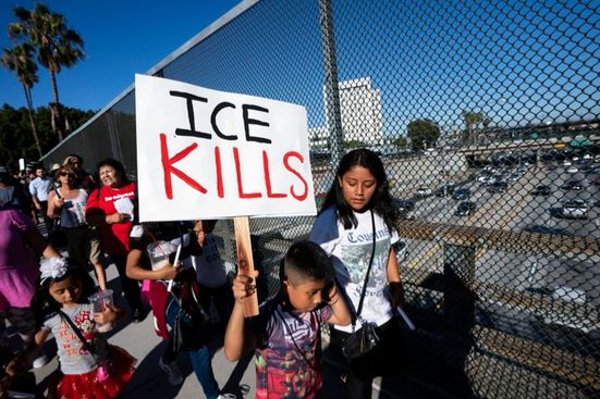 "The image is a high quality photograph of protestors, primarily Hispanic, crossing a bridge above a freeway. One in front, a young boy, carries a stark sign that simply says ""ICE Kills"" in black and red against a white background."