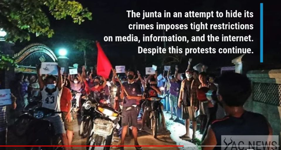 """The image shows night in Burma, protesters holding signs. In white font, superimposed words say: """"The junta in an attempt to hide its crimes imposes tight restrictions on media, information, and the internet. Despite this protests continue."""" The bottom right gives the source as the website yac.news"""