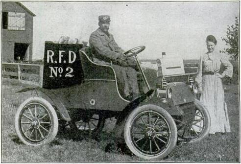 The black-and-white photo shows a uniformed man atop an old-timey automobile. A woman stands behind him. They're in some sort of rural farm setting.