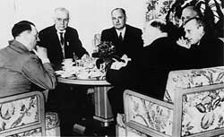 The black-and-white photo shows men in suits sitting around a table.