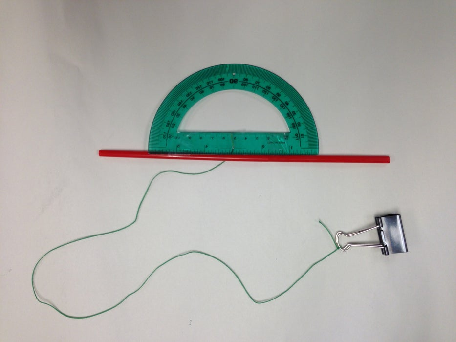 The image shows a DIY clinometer fashioned from a protractor, a straw, clear tape, a straw, and a binder clip.