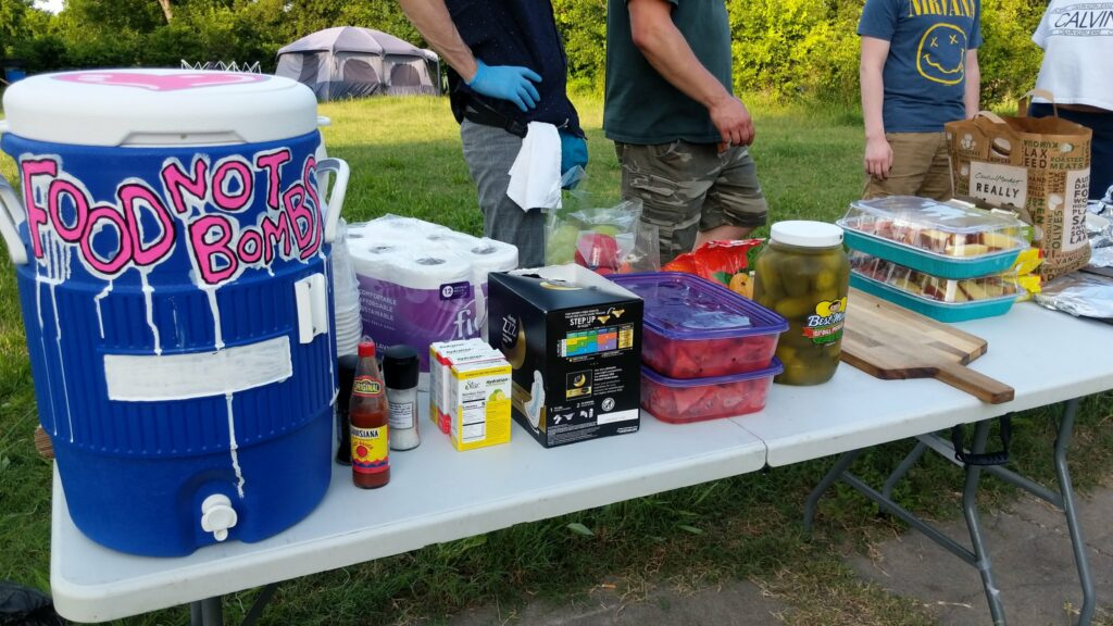 The image shows a folding table set up at a park. On the folding table is a blue water cooler with Food Not Bombs painted on it. Next to the cooler are various food items such as pickles and watermelon. In the background stand what I believe are four Food Not Bombs participants, one with camo pants, another with a Nirvana T-shirt.
