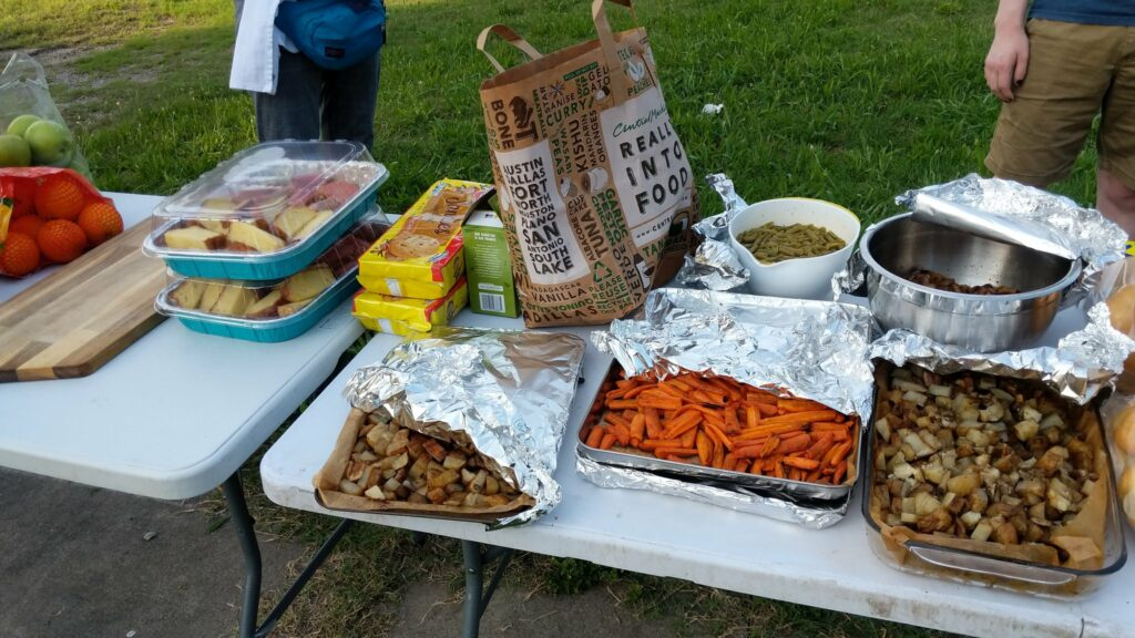 The image shows folding tables in a park with food items set atop. In the background stand what I believe are two members of Food Not Bombs Dallas.
