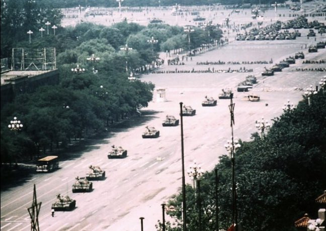 The image shows a man standing defiantly in front of a very long line of Chinese tanks