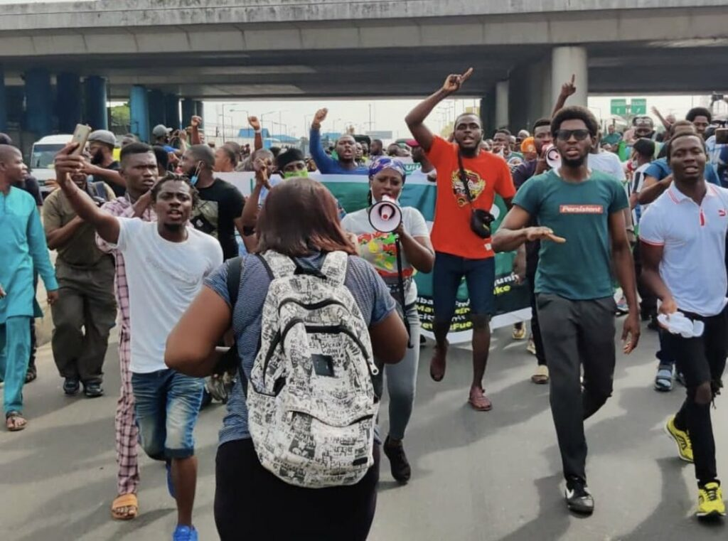 The colorful image shows protestors marching during the day in Nigeria, including one woman with a bullhorn, and many holding their hands in the air