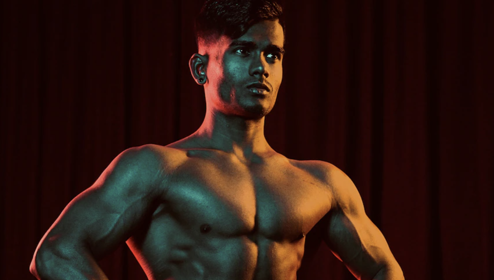 The high contrast picture shows the upper body a man standing with his hands on his hips. A dark red curtain is in the background. The high contrast style of the picture, as well as the stark expression of the very muscular, very symmetrical man, looks almost computer-generated, but it is real.