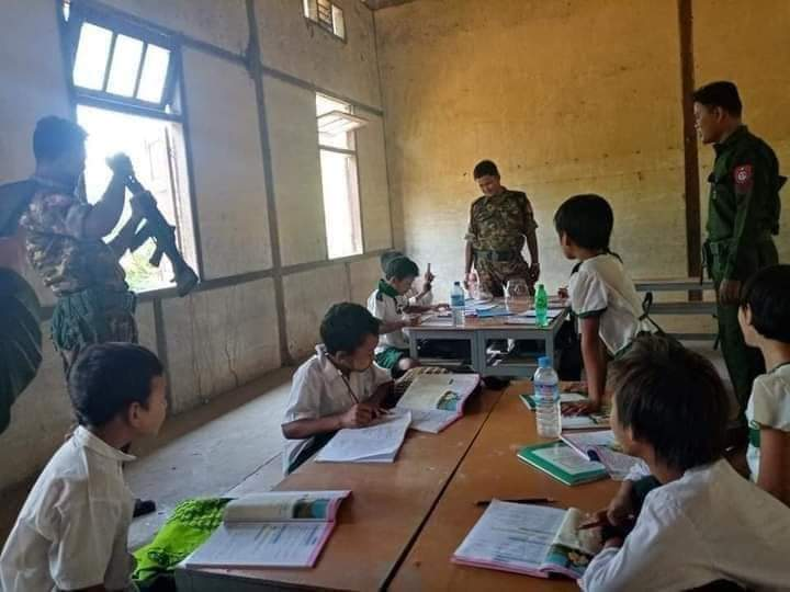 The photo shows a bare schoolroom. Elementary age children sit at tables unmasked, looking a workbooks or the soliders standing around, who are armed and taking the place of teachers