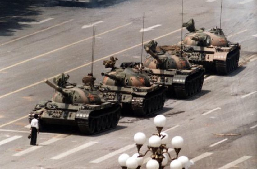 The image shows a man standing defiantly in front of a line of Chinese tanks