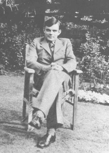The black-and-white image shows Alan Turing sitting in a chair, a frontal photo