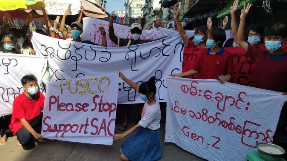 The image shows protesters in a market street of Yangon, some standing, some kneeling, all masked. They are holding signs, upon which is writing mostly in Burmese, else in English