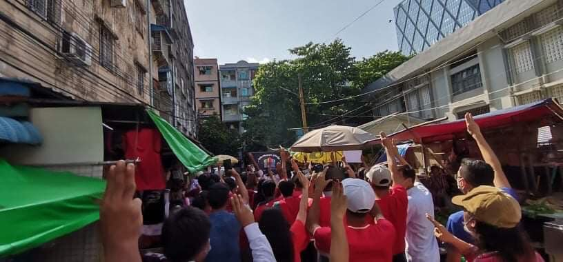 The image shows protestors marching through a market street in Yangon