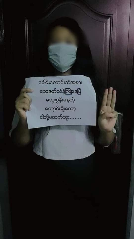 The image shows a masked young girl, perhaps early teens, with her face blurred. She's standing in front of a door and making the three-finger democracy salute. Her other hand holds a sign, upon which is writing in Burmese.