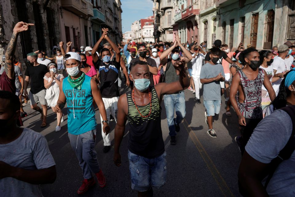 Color photo shows masked Cuban protestors marching, sometimes with their hands in the air.