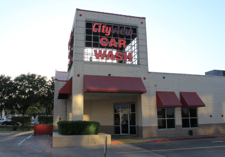 The color photo shows the Cityview Car Wash building in Fort Worth, Texas. The Cityview Car Wash sign is partially burnt out. No people are visible; things seem a little decaying.