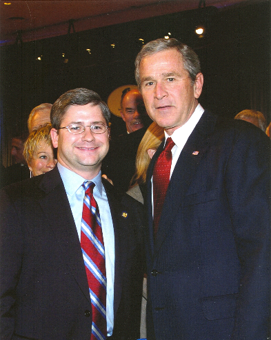 The color photo shows the two suits at some event or other. McHenry, wearing glasses, is smiling huge, probably showing his pleasure at being near one of the top dogs, George W. Bush. Bush II looks like it's just another day on the job of mugging for photos.