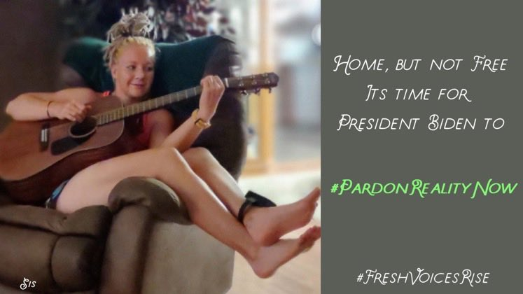 The image shows Reality Winner on home confinement, sitting on a recliner smiling and playing acoustic guitar. She's wearing an ankle monitor. She's not using a pick, but her bare hand, to strum.