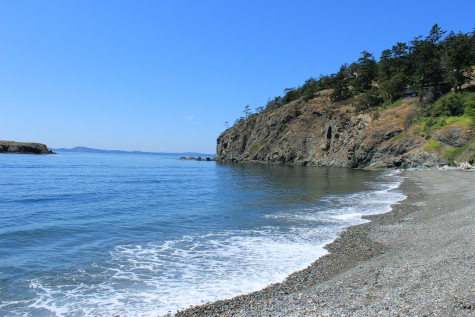 Idyllic color photo shows beach and ocean washing in below a clear blue sky. In the distance are hills, trees, etc.
