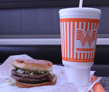 The color photo shows a tray on a table at a Whataburger fast food chain store in Fort Worth, Texas. On the tray sit a large vanilla milkshake (over 900 calories) and a triple meat Whataburger (over 1000 calories). They look disgusting.