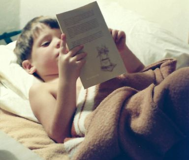The photo shows a child in bed reading. The child is me.